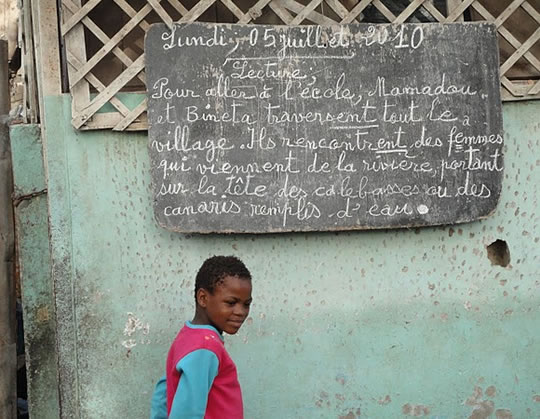 Photo of a Senegalese child standing near a chalkboard.